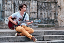 Calm Male Musician Sitting On Stone Stairs In City And Playing Guitar While Looking Away