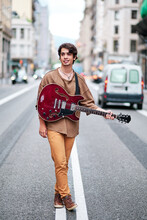 Stylish Content Male Musician With Contemporary Guitar Standing On Roadway In City And Looking Away