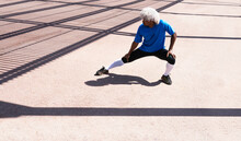 Full Body Black Athlete With Blond Hair Doing Side Lunge On Concrete Ground And Looking Away During Fitness Workout On Sunny Day On City Street