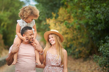 Cheerful Young Blonde Wife And African American Husband With Little Curly Haired Daughter On Shoulders Enjoying Summer Day Together While Walking In Park