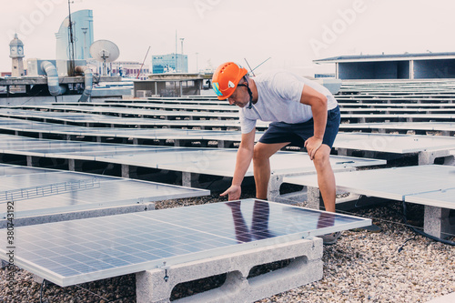 Serious male in helmet worker installing modern solar panels while working in in Fotobehang