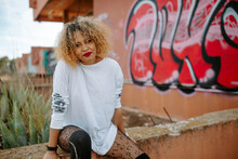 Young African American Female With Red Lips And Curly Hair Sitting On Stone In City Near Wall With Graffiti Looking At Camera