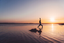 Full Body Side View Of Unrecognizable Slim Female In Activewear Standing In Warrior One Pose With Arms Up In Lake Water While Practicing Yoga During Sunset