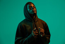 Serious Young African American Male In Black Hoodie Covering Head With Hood Against Green Background In Studio Looking Away