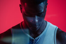 Professional Young African American Sportsman In Sportive Outfit Standing In Studio With Red Neon Illumination With Eyes Closed