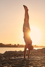 Back View Of Shirtless Male Balancing In Handstand Pose While Practicing Yoga On River Bank During Amazing Sundown