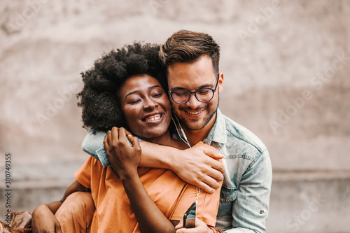 Young cute multicultural couple in love hugging and listening music together over earphones Wallpaper Mural