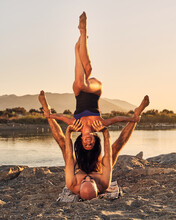 Slim Woman In Handstand With Eagle Legs Supported By Man Lying On Sandy Shore While Practicing Acroyoga Together During Sunset