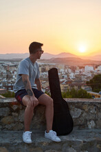 Calm Male Musician With Guitar In Case Sitting On Stone Border And Admiring Breathtaking Sundown