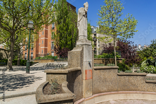 Statue of Saint Denis (first bishop of Paris) holding his own head after beheaded for his Christian faith, Square Suzanne Buisson in Montmartre, Paris France Canvas Print