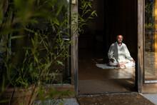 Senior Man Practicing Chi Kung Meditation In Lotus Position In Studio