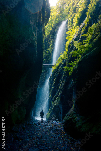 Back view of unrecognizable person walking of spectacular scenery of waterfall in long exposure in woods with green plants in highland area - 380751929
