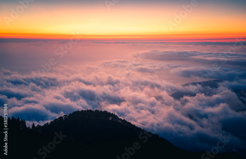 Majestic landscape of mountain range covered with clouds and valley with trees under blue cloudless sky