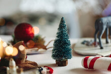Small Green Fir Tree Toy Placed Near Christmas Present Wrapped In Craft Paper On Table With Decorations Against Blurred Glowing Garland