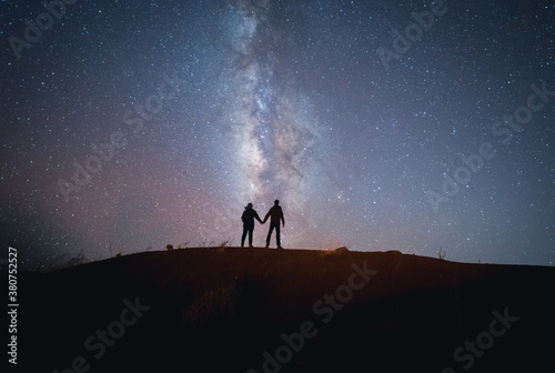 Back view of unrecognizable tender traveling couple standing on hill holding hands while admiring spectacular scenery of milky way over mountainous in starry night