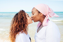 Side View Of Smiling Mother And Daughter Kissing Each Other While Standing On Beach