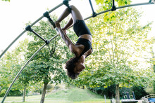 Young Woman Hanging Upside Down On Arched Ladder In Park