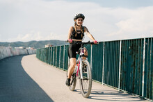 Low Angle Of Confident Young Female Bicyclist In Sportswear And Helmet Riding Bike On Fenced Curvy Paved Track While Training Alone In Summer Day