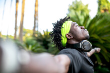 Young African American Male Athlete In Sportswear With Headphones On Neck Keeping Open Arms And Looking Away Thoughtfully While Standing In Green Tropical Park
