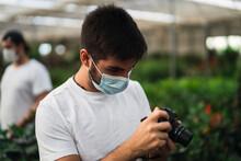 Chico Joven Con Mascarilla En Invernadero Tocando Plantas