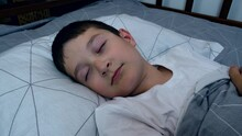 A Boy Lying In Bed At Night An...