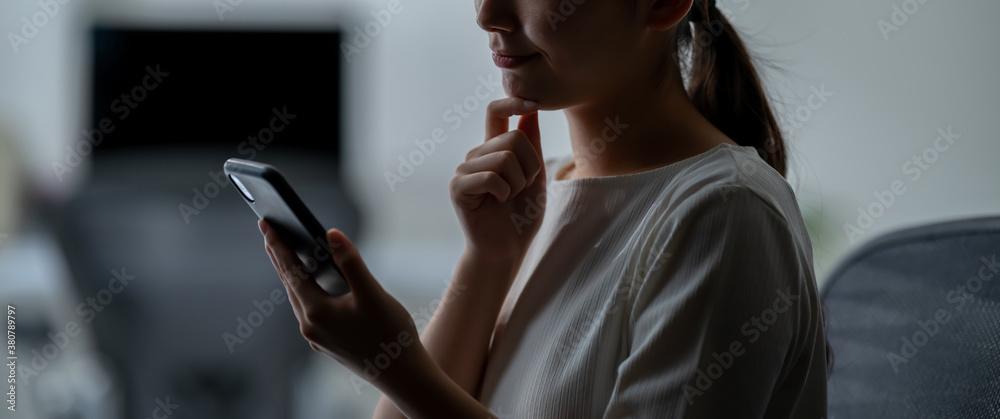 Fototapeta スマートフォンを見て考える女性