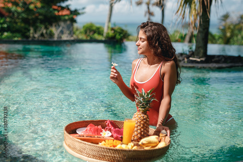 Fototapeta Pretty smiling young woman in red swimsuit  is preparing to eat breakfast with tropical fruits in the swimming pool