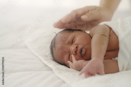 Obraz na plátně african american new born baby lying on white bed