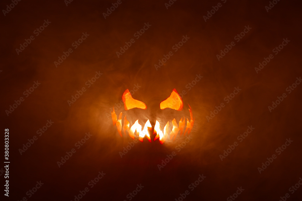 Fototapeta Scary Halloween jack o lantern face glowing in smoke and fire.