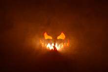 Scary Halloween Jack O Lantern Face Glowing In Smoke And Fire.