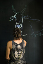 Artist Drawing A Cow On Wall With Projector