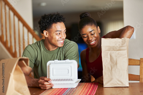 Fototapeta african american couple sitting at table looking at food delivery obraz