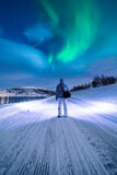 Man walking on a snowy road under northern lights