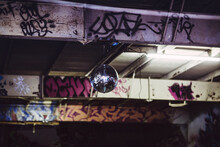 Disco Ball Hanging From The Ceiling Of A Warehouse Party