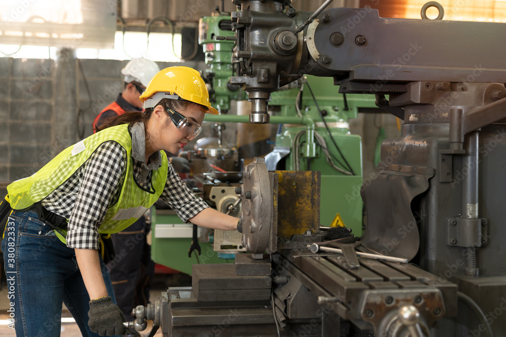 Fototapeta Portrait of confident female worker wearing hard hat and safety glasses working in industrial. Technician engineer control machines in the factory on business day. Concept of workplace gender equality