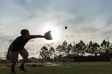 A Boy Catches A Ball At Sunset