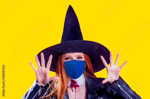 Valokuvatapetti redhaired ginger woman wearing black leather jacket for halloween party ,studio yellow background