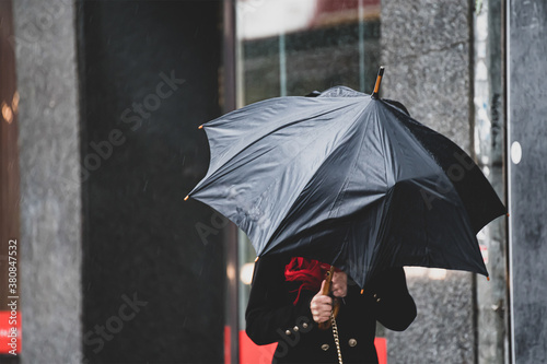 Fototapeta A woman has difficulty holding an umbrella from strong winds in rainy weather. obraz