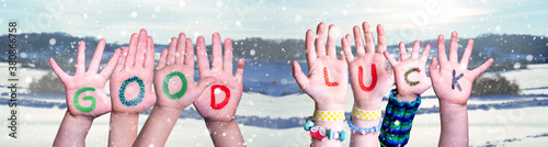 Fototapeta Kids Hands Holding Colorful English Word Good Luck. Snowy Winter Background With Snowflakes obraz
