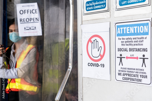 Fototapeta Caution sign in factory warning to industry labor worker to prevent Covid-19 Coronavirus spreading during job business reopening period after epidemic crisis . Working safely concept . obraz