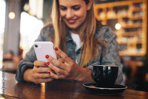 Fototapeta Woman using her mobile phone at a coffee shop obraz