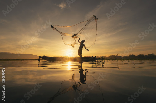 Photo Silhouette Fisherman casting or throwing a net for catching freshwater fish in nature lake or river with reflection in morning time in Asia in Thailand