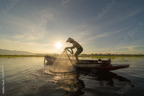Tela Silhouette Fisherman casting or throwing a net for catching freshwater fish in nature lake or river with reflection in morning time in Asia in Thailand