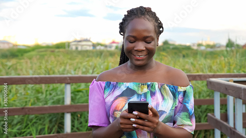 Foto happy young African-American woman in stylish blouse surfs internet with new sma