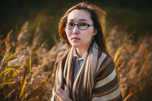 A Beautiful Girl With Glasses And Loose Hair Of The Mongoloid Race Stands In The Middle Of Tall Grass In The Cool Autumn Time And Is Illuminated By The Sun's Rays. Early Autumn.