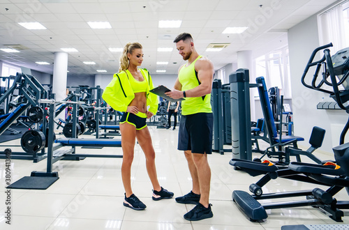 Obraz Beautiful young woman with her personal trainer at the gym discuss her progress on a clipboard held by the man. Healthy lifestyle - fototapety do salonu