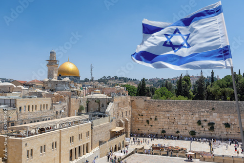 An Israeli flag blows in the wind as jewish orthodox believers read the Torah and pray facing the Western Wall, also known as Wailing Wall or Kotel in Old City in Jerusalem, Israel Canvas Print