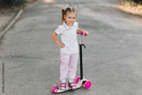 Little girl with pigtails and hairpins on her hair, the child is standing, smiling on a multi-colored scooter, holding the wheel Canvas Print
