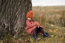 Cute Little Preschooler Girl In An Orange Hat And A Brown Coat Leans Back On A Huge Old Tree And Sits On The Grass. Autumn Horizontal Photo Of A Child