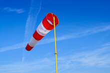A Striped Meteorological Windsock On A Background Of A Blue Sky